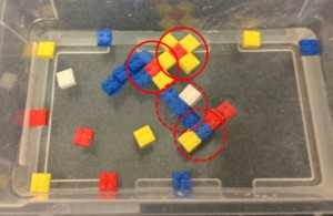 Self-assembly of magnetized 2x2 Lego bricks. What do you notice about the regions circled in red? Why do you think this is the optimal arrangement for these Legos? How would the arrangement be different if all Legos attracted all other Legos, as in the case of the cereal? (Click to enlarge.)
