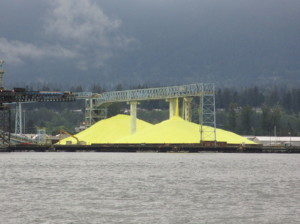 One of the major reasons for iron sulfide's very low cost is the low cost of sulfur, which is essentially a waste product. This image shows a sulfur stockpile in Vancouver Harbor.  (Wikimedia Commons)
